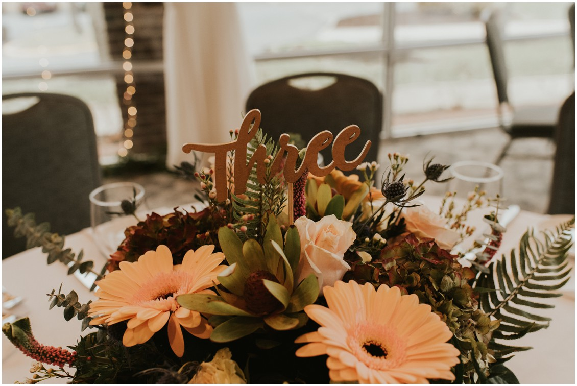 Detail of centerpiece and table number with twinkle lights in background in winter wedding | My Eastern Shore Wedding | Bear Trap Dunes | Coastal Tented Events