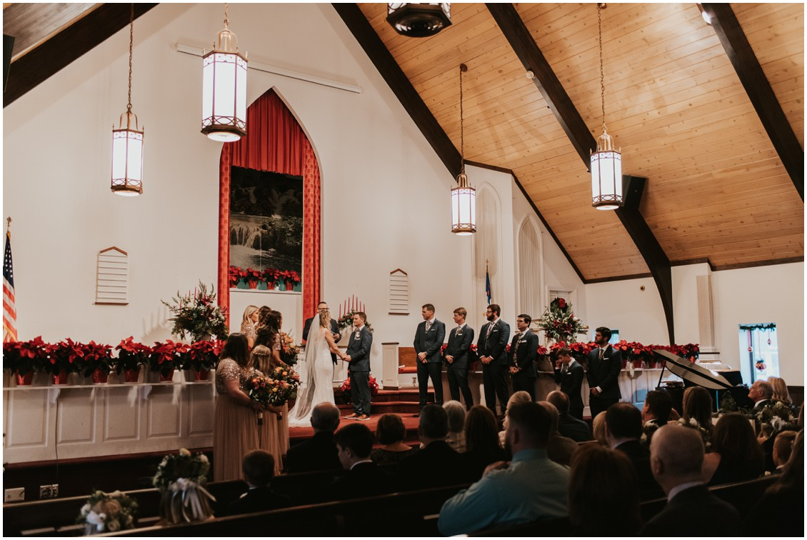 Bride and groom getting married in church in winter wedding  with poinsettias | My Eastern Shore Wedding | Bear Trap Dunes | Coastal Tented Events
