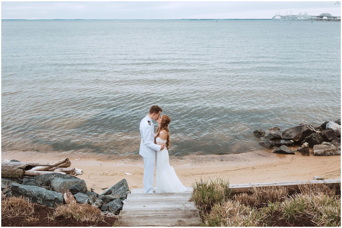 Bride and Groom in Naval sailor uniform kissing on the beach with Chesapeake Bay sunset in the background | My Eastern Shore Wedding | Chesapeake Bay Beach Club
