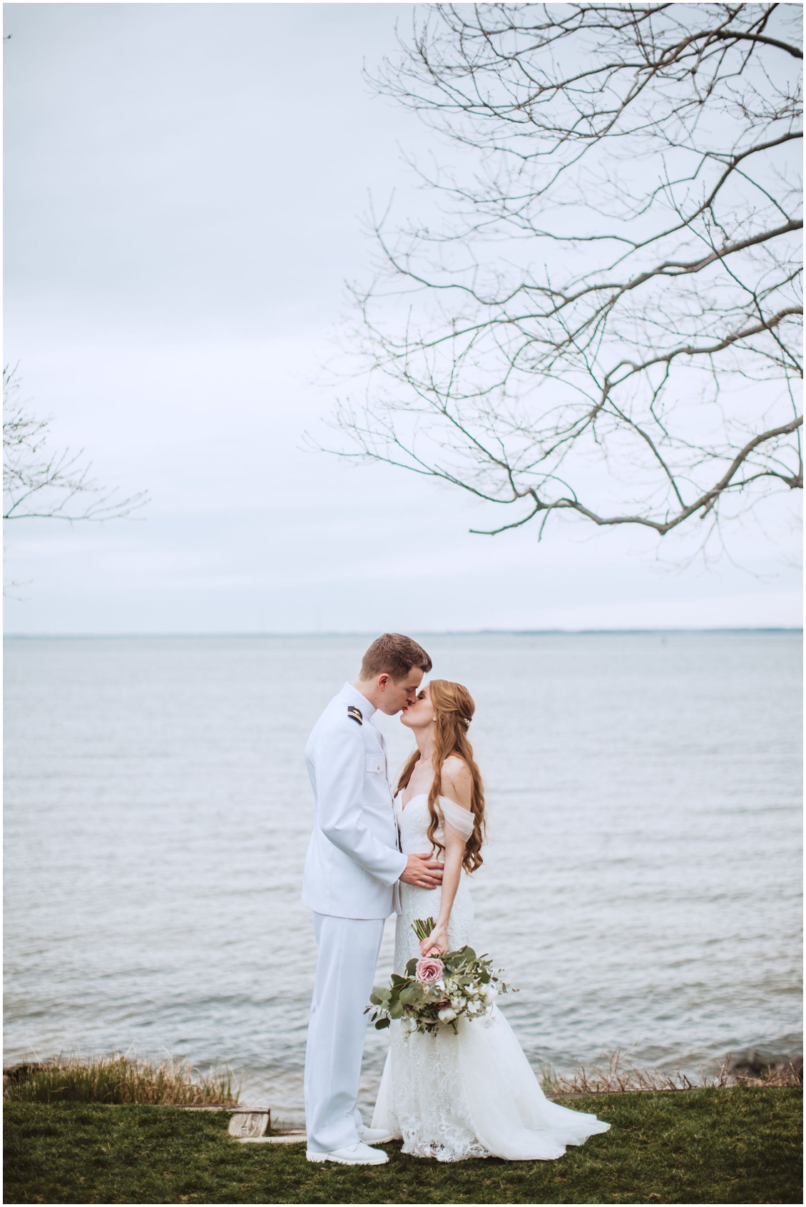 Bride and groom in naval sailor uniform kissing in front of Chesapeake Bay at sunset| My Eastern Shore Wedding | Chesapeake Bay Beach Club