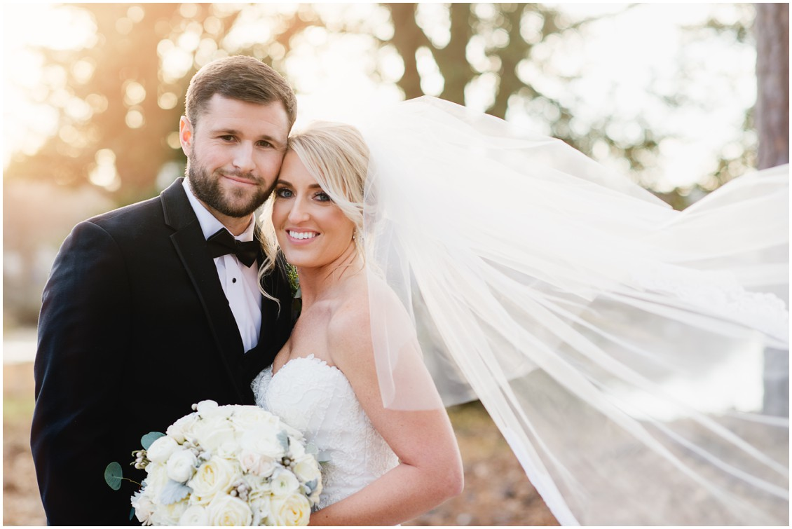 Bride and groom portrait in warm winter sun with veil blowing in the wind | My Eastern Shore Wedding | Karena Dixon | Monteray Farms