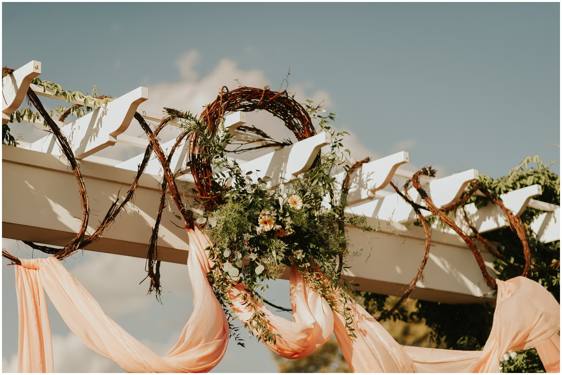 Raffia hoops and blush fabric decorating arch on veranda of The Clubhouse at Baywood | My Eastern Shore Wedding