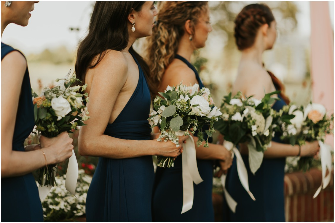 Bridesmaids holding bouquets during ceremony at the Clubhouse at Baywood | My Eastern Shore Wedding