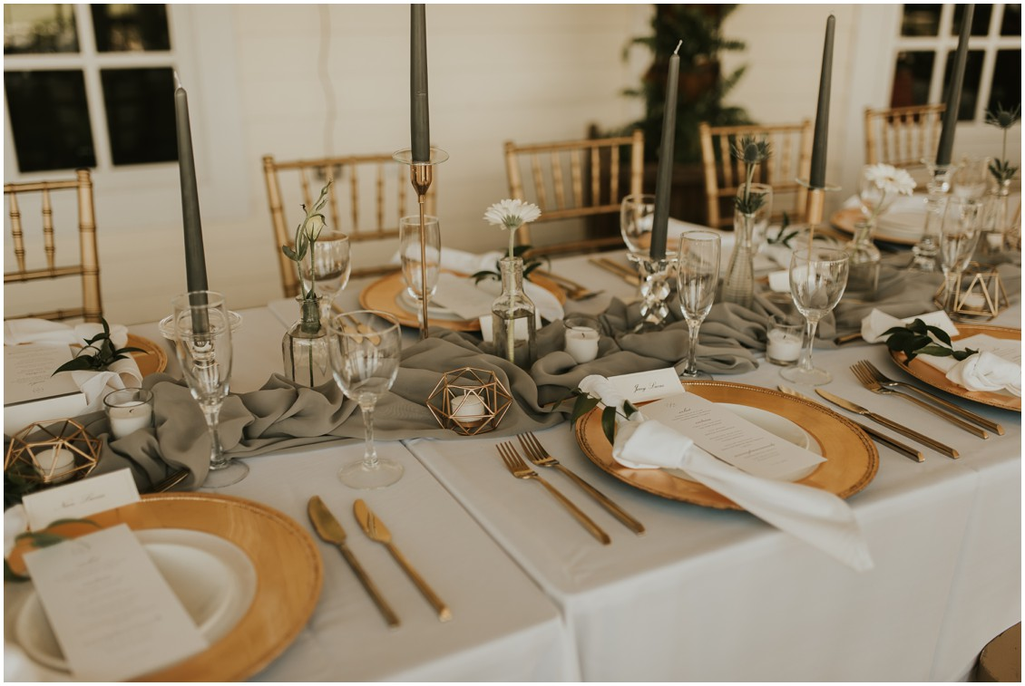 Detail of table with gray tapered candles and runner with gold chargers| My Eastern Shore Wedding
