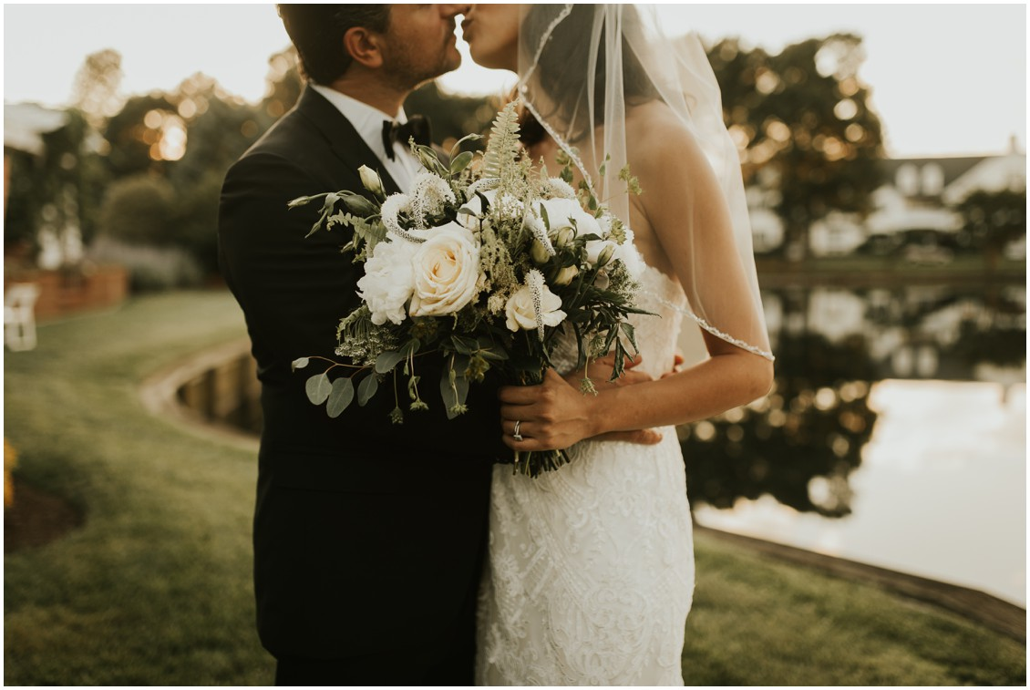 Bride and groom kissing holding bridal bouquet | My Eastern Shore Wedding