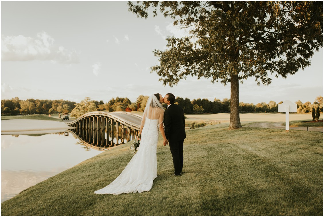 Bride and groom kissing on golf course next to water at the Clubhouse at Baywood  | My Eastern Shore Wedding