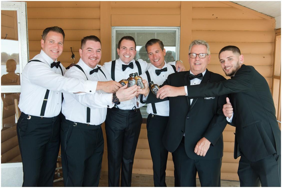 Groom and groomsmen holding whisky bottles | Brittland Manor | Rob Korb | My Eastern Shore Wedding