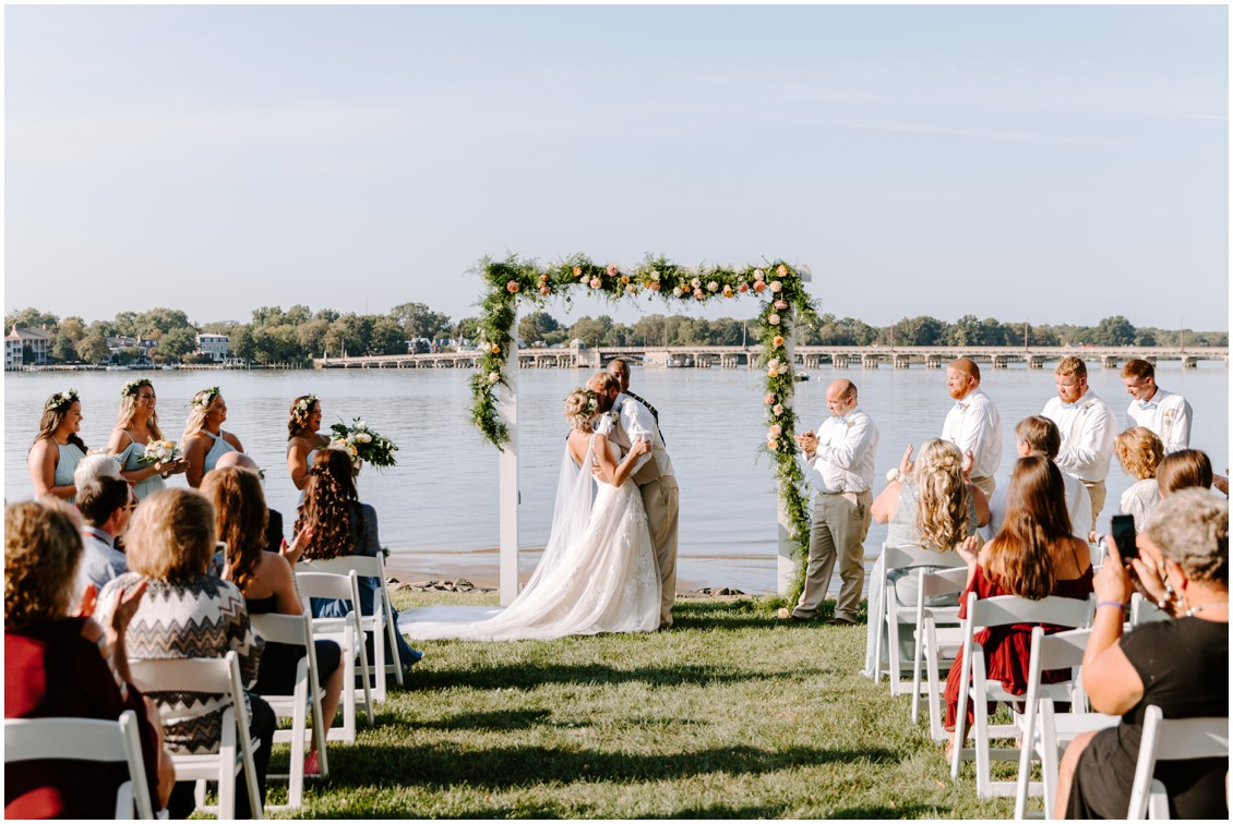 Bride and groom kissing under decorative arch with soft greenery and roses | My Eastern Shore Wedding | Sherwood Florist | Eastern Shore Tents and Events
