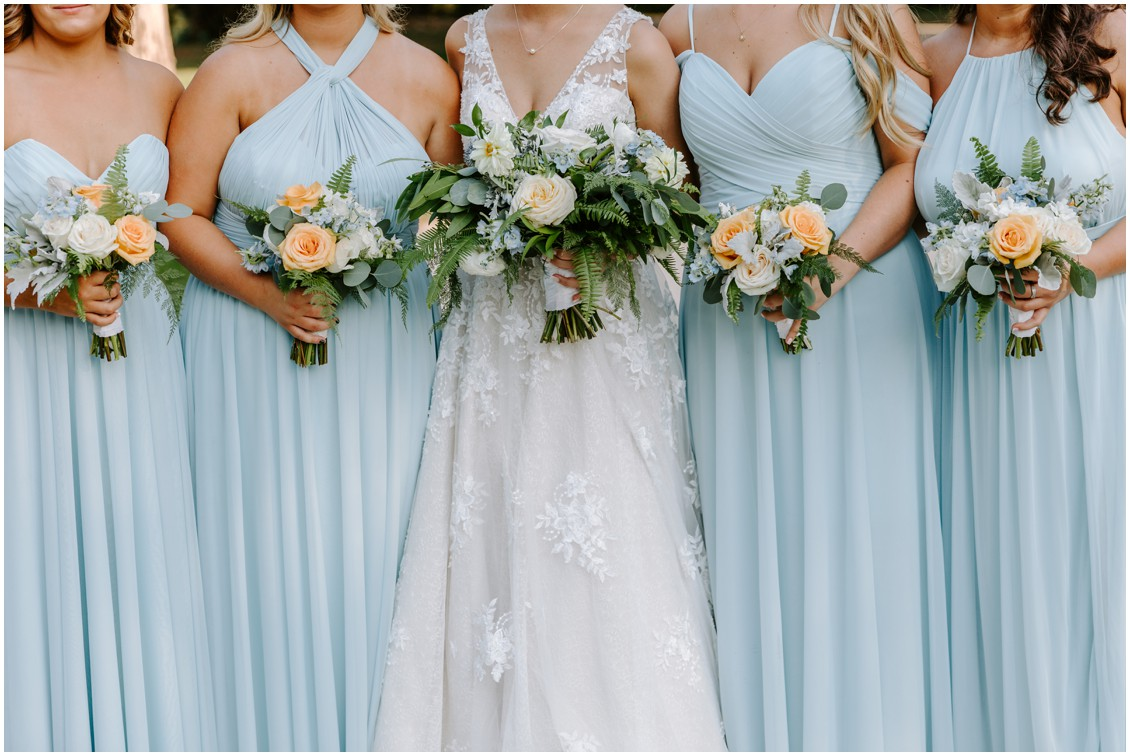 Bride with bridesmaids in soft blue dresses with pops of peach| My Eastern Shore Wedding | Sherwood Florist |