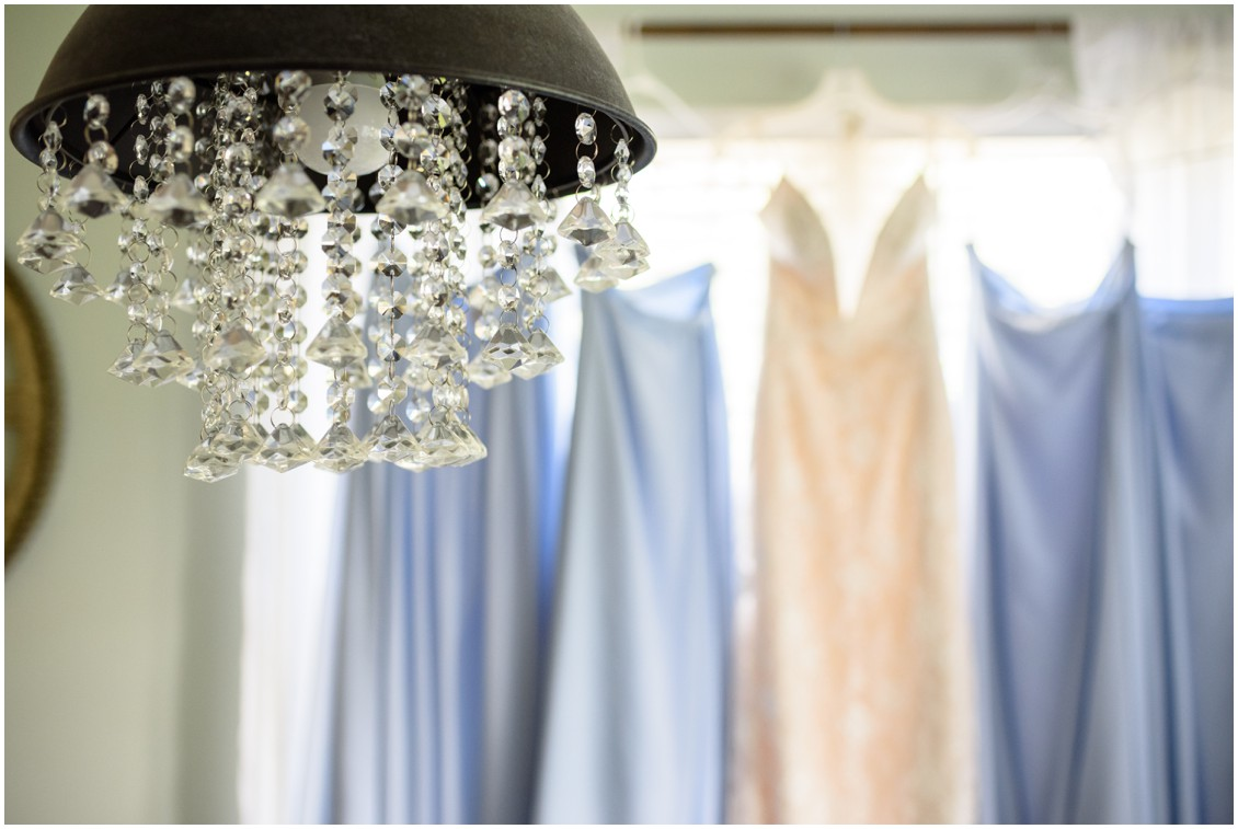 Blue bridesmaid dresses and bridal gown out of focus behind chandelier | My Eastern Shore Wedding | J. Nicole Photography