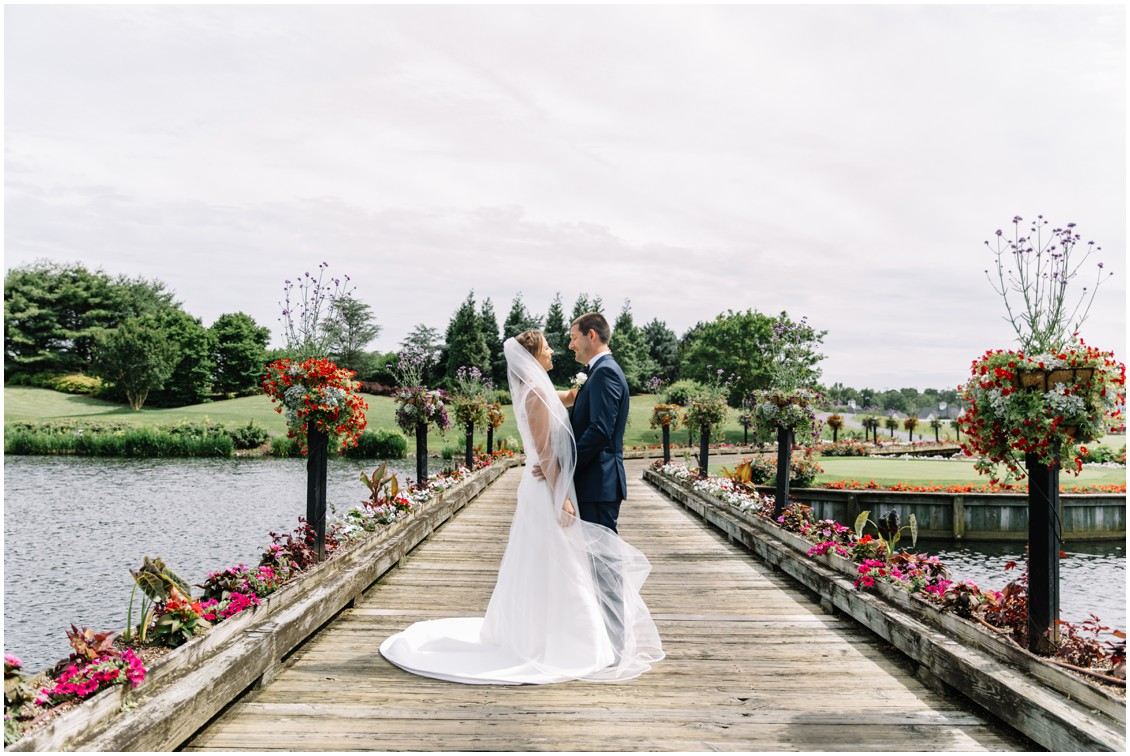 Abundant beauty at Baywood bride and groom on decorated bridge | My Eastern Shore Wedding | The Clubhouse at Baywood