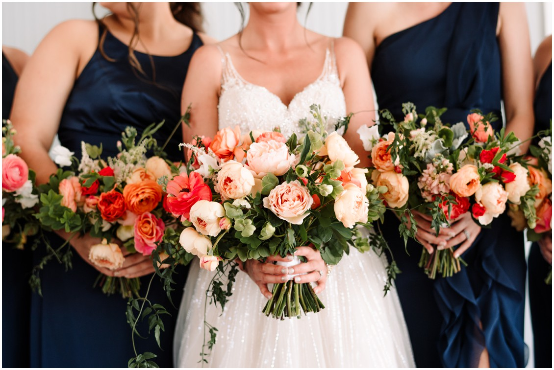 Bride and bridesmaids in dark blue dresses with bright bouquets at bayside celebration | My Eastern Shore Wedding | Chesapeake Bay Beach Club