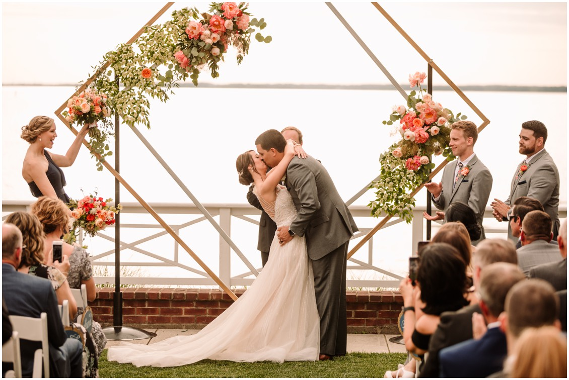 Bride and groom first kiss as married couple with view of Bay and bright flowers | My Eastern Shore Wedding | Chesapeake Bay Beach Club