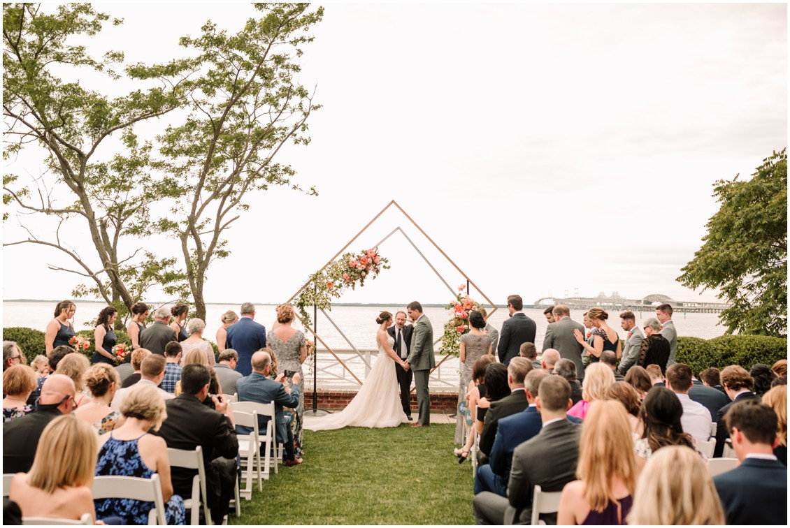 Bride and groom at altar with view of Bay and bright flowers | My Eastern Shore Wedding | Chesapeake Bay Beach Club