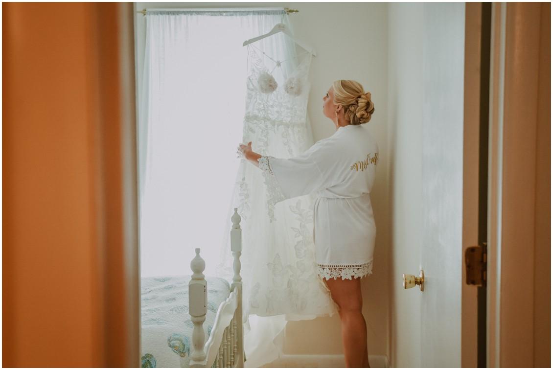 Bride looking at bridal gown summer wedding | My Eastern Shore Wedding