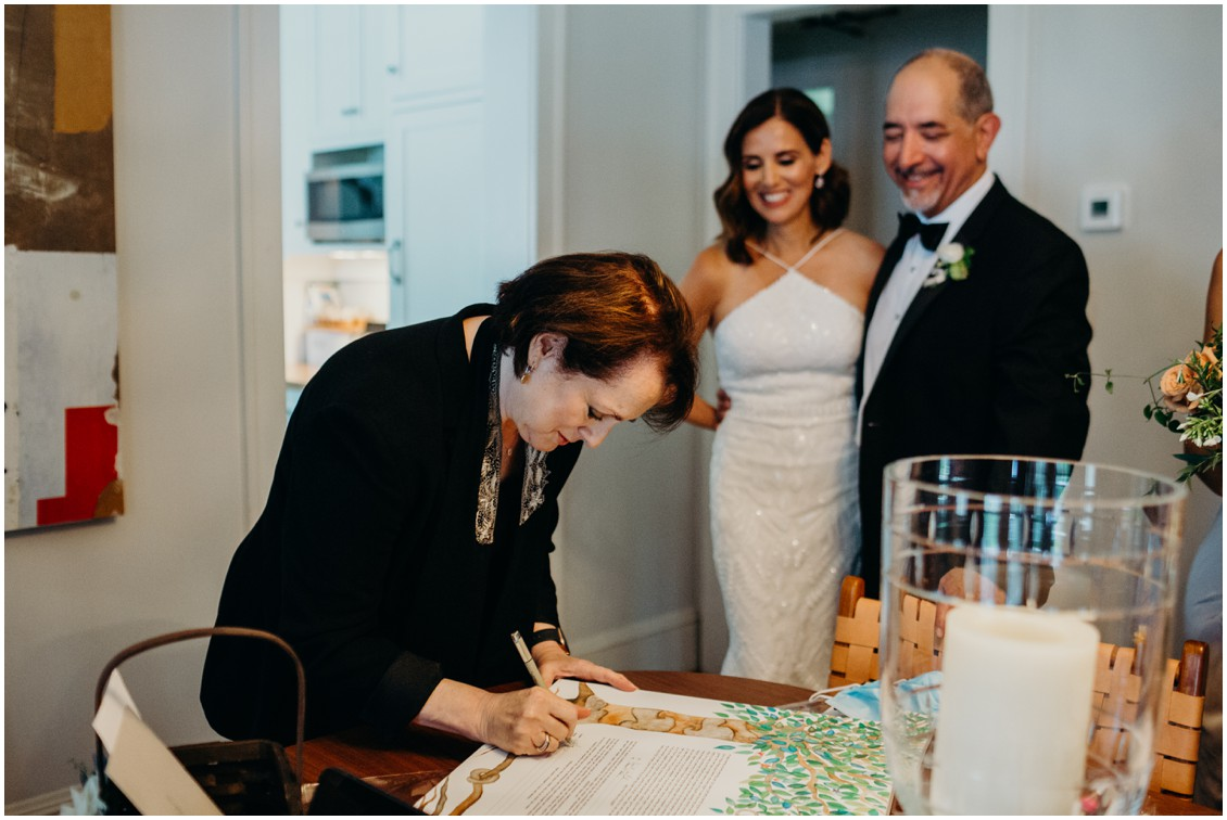 Bride and Groom with rabbi signing Ketubah | My Eastern Shore Wedding | Sherwood Florist