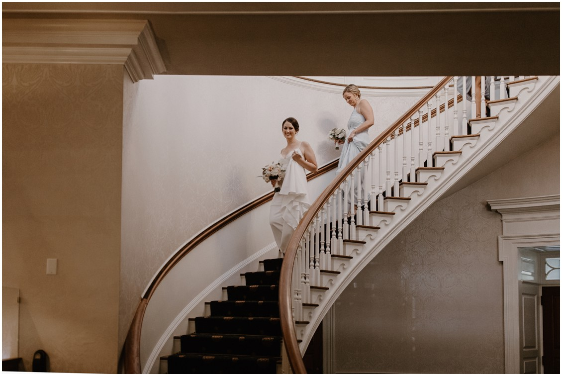 Bride in simple and stunning gown coming down elegant staircase | My Eastern Shore Wedding |The Tidewater Inn