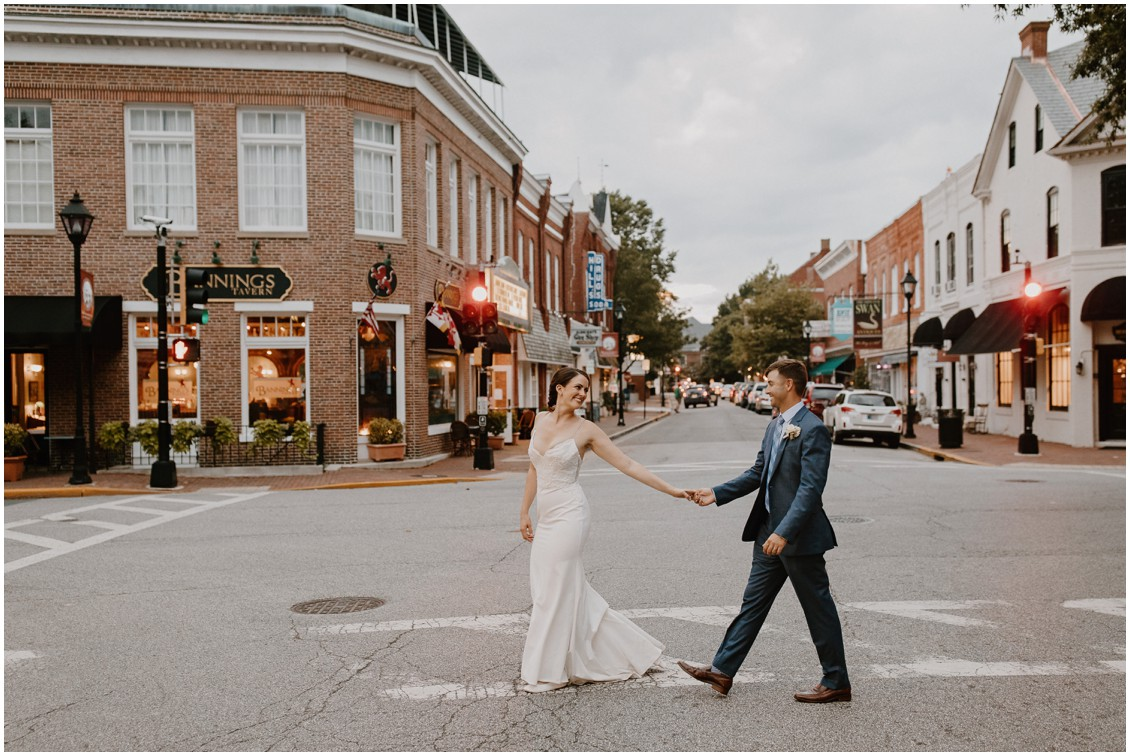 Bride in simple and stunning dress and groom walking through downtown Easton | My Eastern Shore Wedding | The Tidewater Inn