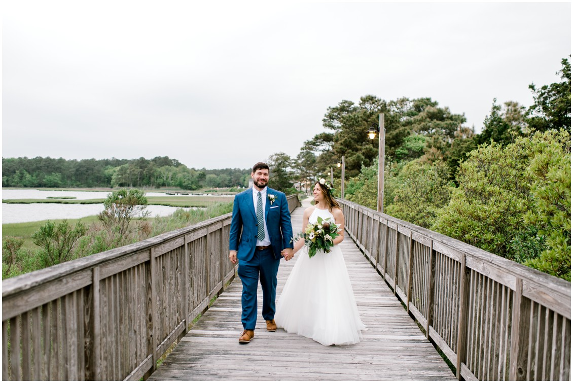 Bride and groom walking on pier naturally beautiful wedding | My Eastern Shore Wedding | Erin Wheeler Photography | Bayside Resort Golf Club