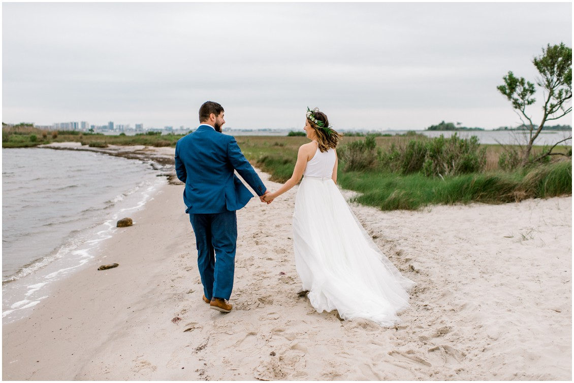 Bride and groom walking on beach following ceremony | Naturally Beautiful Bayside Wedding | My Eastern Shore Wedding | Erin Wheeler Photography | Bayside Resort Golf Club