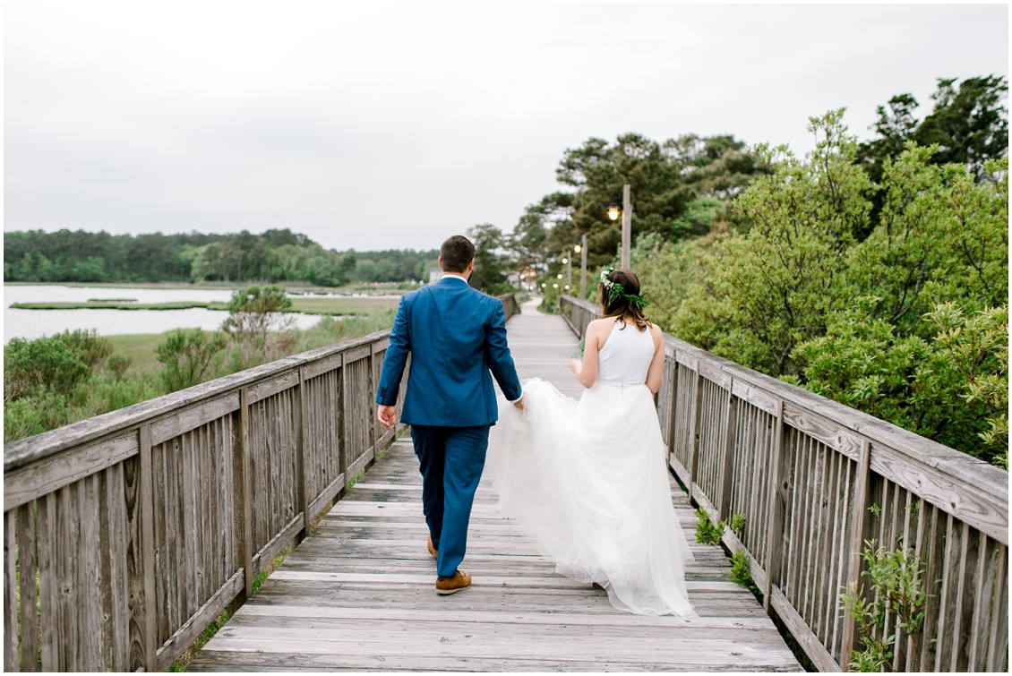 Bride and groom walking on pier | Naturally Beautiful Bayside Wedding | My Eastern Shore Wedding | Erin Wheeler Photography | Bayside Resort Golf Club