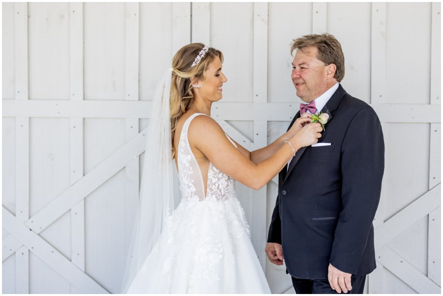 Bride helps her Dad with his boutonniere.